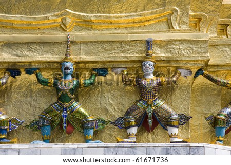 The famous golden guards holding the Emerald Buddha Temple on their shoulders. Grand Palace, Bangkok, Thailand.