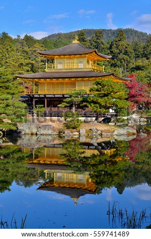 The famous golden pavilion, or kinkakuji in Japanese, and nearby trees in green and autumn color as well as blue sky are beautifully reflected in clear still lake. Taken In Kyoto, Japan.