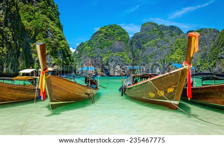 The famous heavenly beach Maya Bay on Phi Phi Islands with colorful longtail boats and limestone hills in the background, Thailand - stock photo