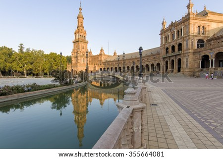 The famous historical Spanish Square in Seville, built for the Ibero-American Exhibition of 1929. Plaza de Espana is a semi-circular brick building, with a tower at either end. - stock photo