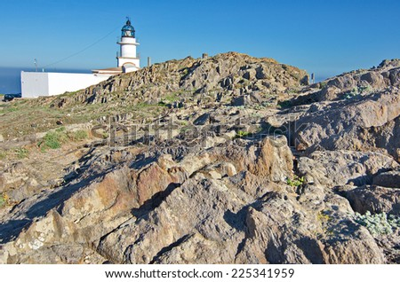 The famous lighthouse in the wind beaten and dry rocky landscape of the Cape in Cap de Creus peninsula, Catalonia, Spain.  This extraordinary landscape inspired some Salvador Dali works. - stock photo