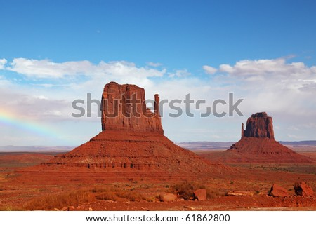 """The famous """"Mittens"""" in Monument Valley. The cliffs of red sandstone on the background of the cloudy sky - stock photo"""
