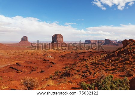 "The famous ""Mittens"" in Monument Valley. The cliffs of red sandstone on the background of the cloudy sky"
