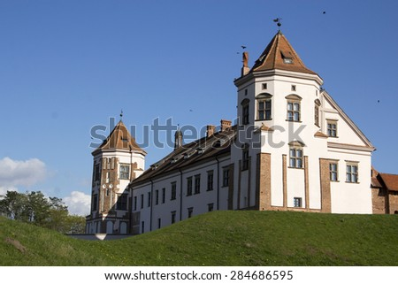 The Famous Old Castle in Belarus. Sunny day, blue sky, white stone tower and walls. Green grass.