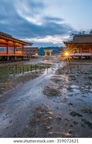 The famous orange floating shinto gate (Torii) and Itsukushima shrine, Miyajima island of Hiroshima prefecture, Japan under Golden Dramatic Twilight Sky at Dusk in Summer Sunset Low Tide - stock photo