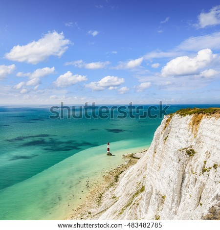 The famous red and white striped lighthouse at the foot of the chalk cliffs at Beachy Head, Sussex, England, on a beautiful summer's day