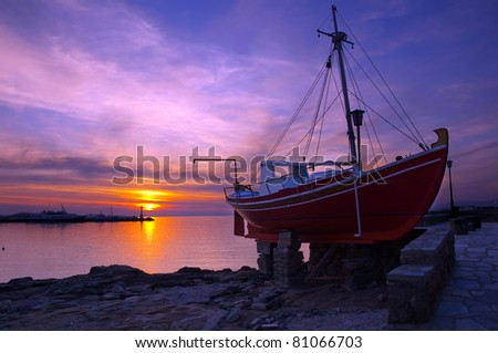 The famous red boat of Mykonos at sunset. Greece. - stock photo
