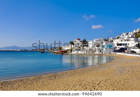 The famous Tavern on the sea mirror of the bay of the island of Mykonos with a red boat and the church - stock photo