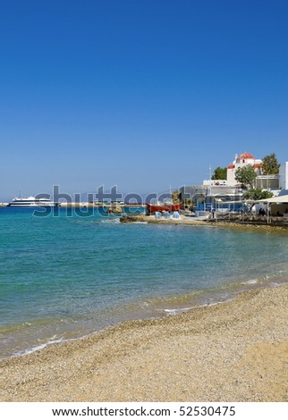 The famous Tavern on the sea shore of the bay of the island of Mykonos with a red boat and the church - stock photo