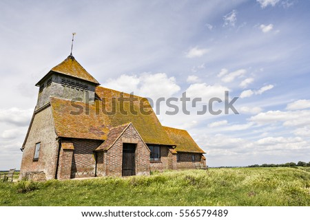 The famous 18th century Church of Thomas A Becket at Fairfield, Romney Marsh, Kent, England, still in use today, under a lovely soft summer sky.