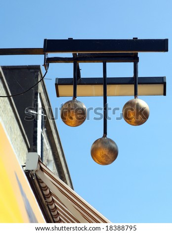 The famous three gold balls sign of a pawnbroker's shop, above a street in Great Yarmouth, Norfolk, eastern England. - stock photo