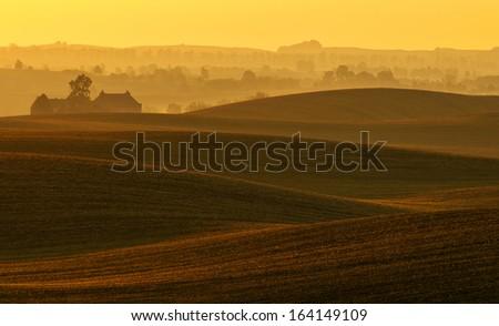 The farm on undulating fields of autumn - stock photo