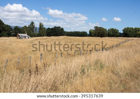 The farm, wooden fence diagonally crosses the dry, golden field, with a country house in the distance. - stock photo