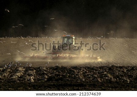 The farmer in his tractor working in the field - stock photo