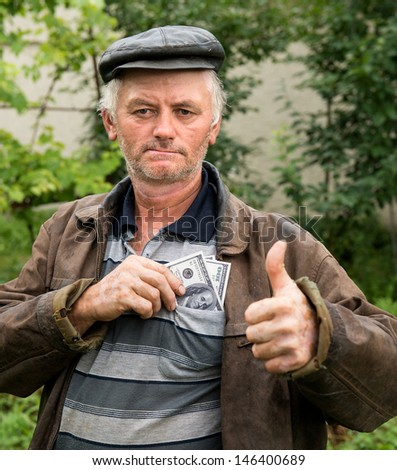 The farmer with money in his jacket on natural background - stock photo
