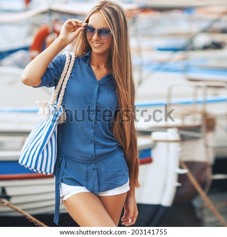 the fashionable portrait of glamourous model in sunglasses with a striped bag walks on city streets - stock photo