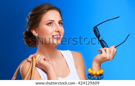 The fashionable young woman in sunglasses holding bag - stock photo