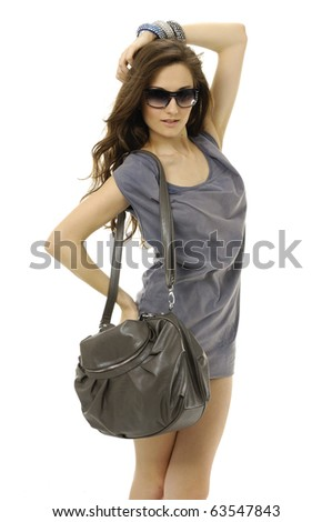 The fashionable young woman in sunglasses with handbag