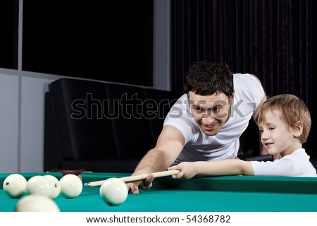The father and the son play billiards - stock photo