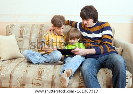 The father and two boys play on tablet PC - stock photo