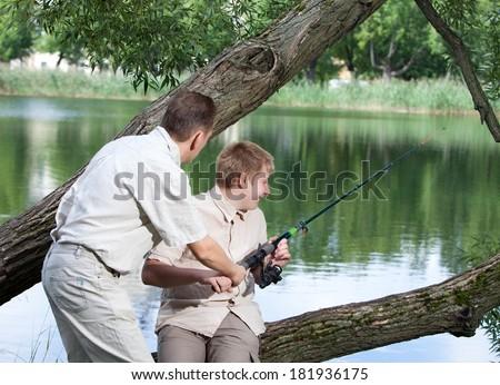 The father asks a fishing tackle from the son too to fish - stock photo