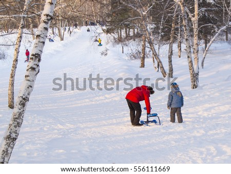 The father helps his son to correct snowmobile, rolled down hill