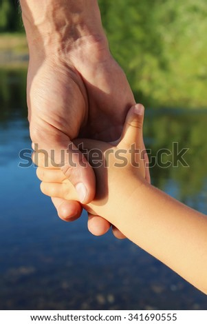 The father holds the child by a hand on walk - stock photo