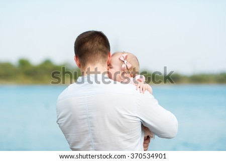 The father holds the little daughter on hands. It costs a back.