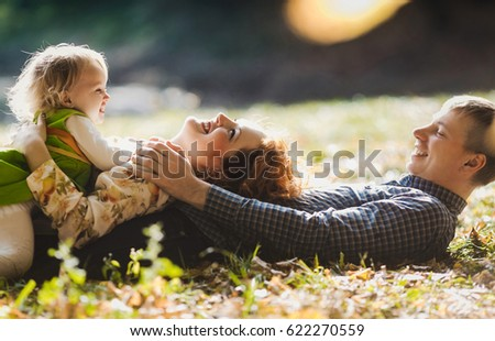 The father,mother and daughter lie on the grass