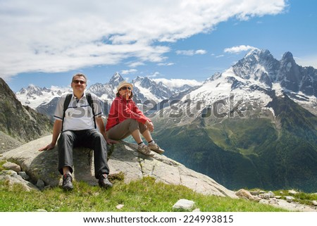 the father of an adult daughter sitting on the stone in the mountains and admire the scenery - stock photo