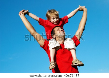The father playing with son against sky - stock photo