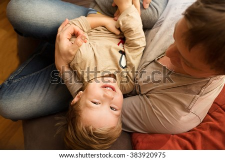 the father plays with the kid in the room - stock photo