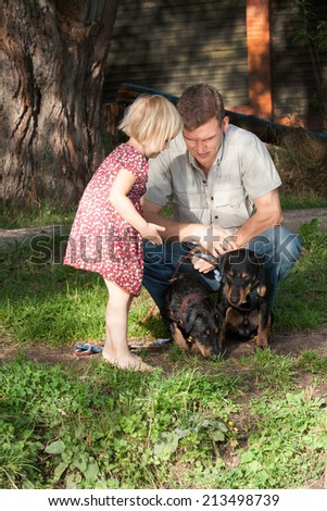 The father to the daughter about something talk, looking at sitting puppies Jagdterriers - stock photo