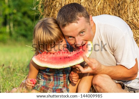The father with the child eats water-melon against hay