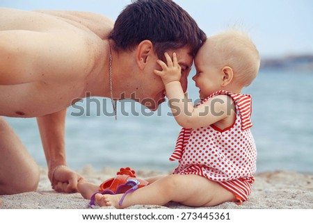 The father with the daughter is played on a beach - stock photo