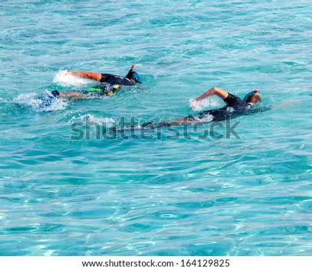 The father with the son in the sea with the equipment for a snorkeling - stock photo