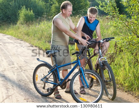 The father with the son on bicycles - stock photo