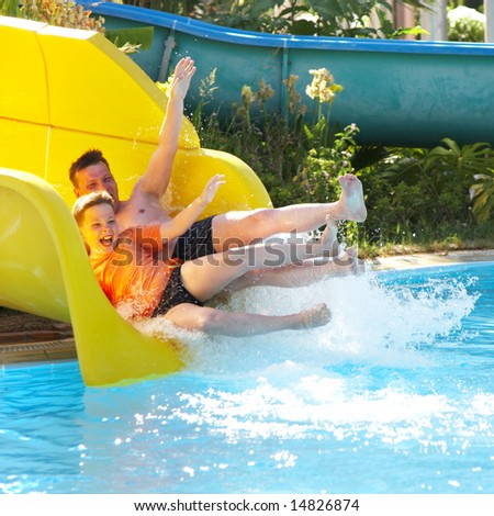 The father with the son on waterslide... - stock photo