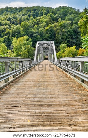 The Fayette Station Bridge, with its wooden deck, crosses West Virginia's New River in Fayette County. The span is also called the Tunney Hunsaker Bridge. - stock photo