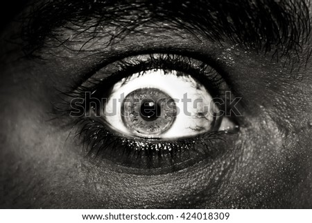 The fear in his eyes. Very expressive eyes close-up and in black and white - stock photo