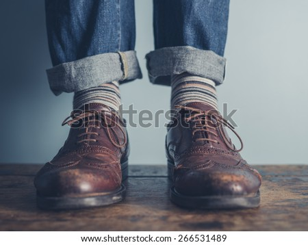 The feet of a man standing on a wooden floors wearing stripey socks and leather shoes - stock photo