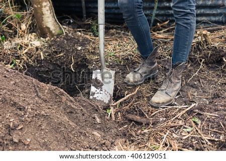 The feet of a person in boots standing by a hole with a spade - stock photo