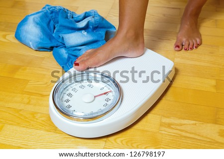 the feet of a woman standing on a bathroom scale