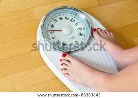 the feet of a woman standing on bathroom scales to turn - stock photo