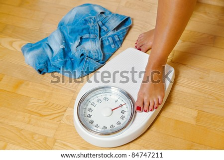 the feet of a woman standing on scales - stock photo