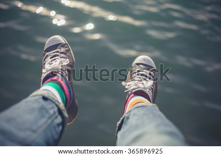 The feet of a young man dangling over water - stock photo