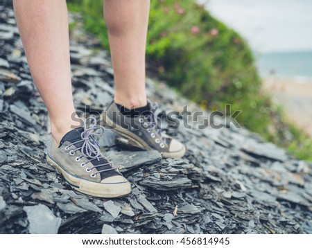 The feet of a young woman standing on some stones outside near the coast