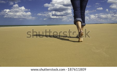 The feet of a young woman walking on the sand of a sunny beach. - stock photo