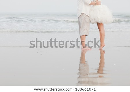 The feet of the bride and the groom playing on the beach - stock photo