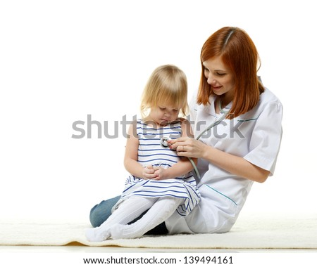 The female doctor with a stethoscope and the small patient sit on a white background. Pediatrics. - stock photo